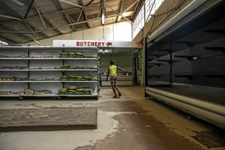 A young boy walks past empty shelves, including those for bread and meat products, in a groceries store in Harare as Zimbabwe is experiencing renewed shortages, on October 9, 2018. - Zimbabwe's moribund economy has hit new lows in recent days with shops struggling to stock shelves, prices of goods such as cooking oil rising rapidly due to panic buying and long queues outside petrol stations. (Photo by Jekesai NJIKIZANA / AFP)