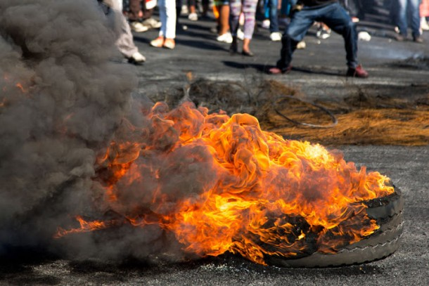 43949080 - protesters against the government burning rubber tyres in the streets in south africa